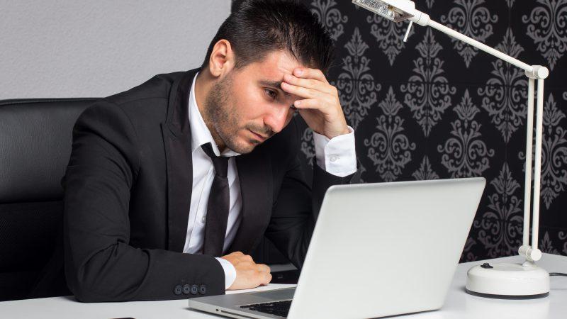 Sfrustrowany trader przed laptopem